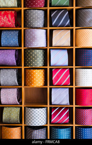 Display of colourful mens' ties, rolled and set between wooden partitions, one compartment empty. - Stock Image