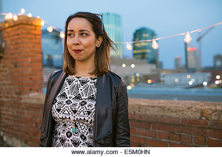 Smiling woman looking away on urban rooftop - Stock Image