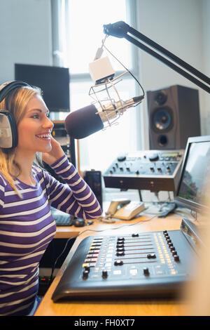 Happy female radio host broadcasting through microphone - Stock Image