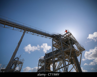 Worker standing on conveyor in quarry - Stock Image