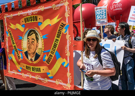 June 30, 2018 - London, UK. 30th June 2018. Lewisham Hospital Unison banner with a portrait of Nye Bevan outside the BBC waiting for the march through London from the BBC to a rally near Downing St to celebrate 70 years of the NHS, and to support its dedicated workers in demanding a publicly owned NHS that is free for all with proper funding and proper staffing and providing a world class services for every community. The protest, organised by the the People's Assembly, Health Campaigns Together, Trades Union Congress, Unison, Unite, GMB, British Medical Association, Royal College of Nursing - Stock Image