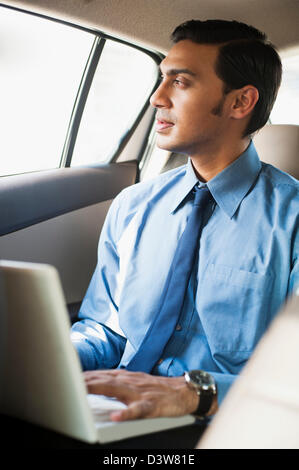 Bengali businessman using a laptop in a car - Stock Image