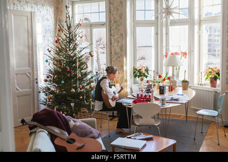 Sweden, Senior woman playing guitar in living room - Stock Image