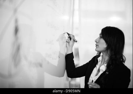 Woman writing on white board - Stock Image