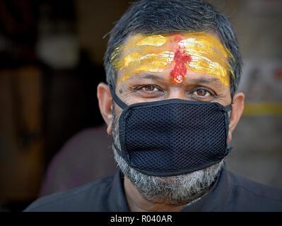 Un fidèle shaivite indien (dévot hindou adorant Shiva) portant un tripundra jaune sur son front porte un masque anti-pollution noir. - Image de l'éditeur