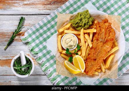 croustillants fish and chips - morue frite, frites de français, tranches de citron, sauce tartare et purée de pois sur plaque sur papier sur une vieille table en bois avec romarin en mor - Image