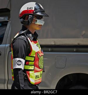 Un officier de police thaïlandais portant un masque antipollution dans la circulation très polluée de Bangkok. Asie du Sud-Est - Image