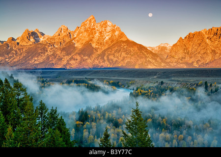 Full moonrise with fog fall color Snake River and Teton Mountains Grand Teton National Park WY - Stock Image