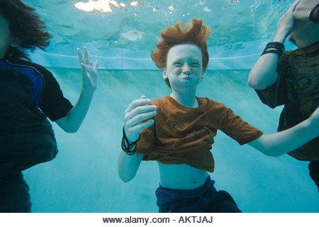 Boys swimming underwater - Stock Image