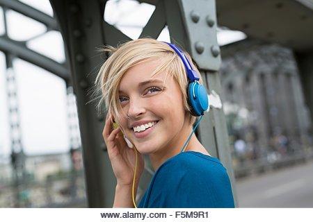 Happy young woman wearing headphones on bridge looking over her shoulder - Stock Image
