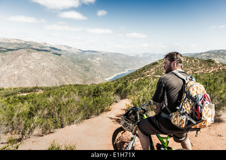 Downhill mountain biker looking at view - Stock Image