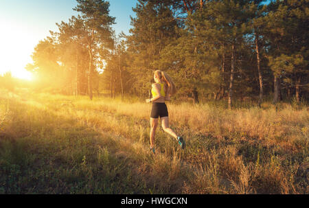 Young sporty girl running on a field near the trees at sunset in summer. Athlete running on the off road in the - Stock Image