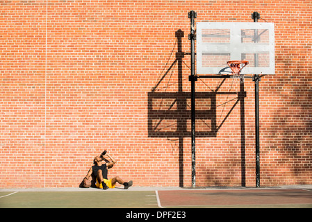 Basketball player resting on court - Stock Image
