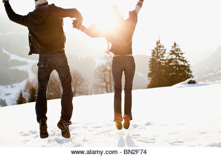 Couple jumping outdoors in snow - Stock Image