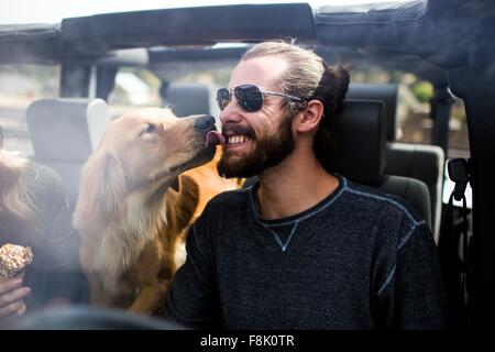 Dog licking young mans bearded face in jeep - Stock Image