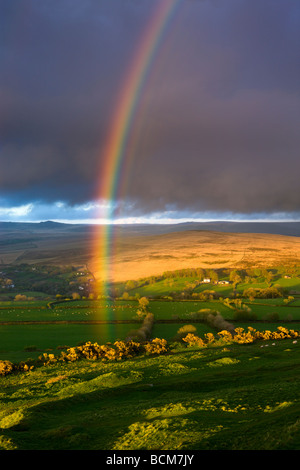 Rainbow above rolling farmland on the edges of Dartmoor National Park Devon England Spring April 2009 - Stock Image