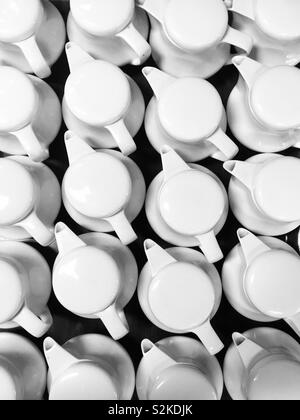 Group of white tea pots in rows from above. Shapes and patterns form, looking down on multiple white teapots on black table, restaurant or cafe background. - Stock Image