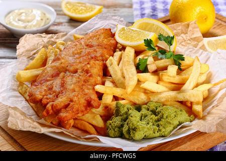 chips de poisson et frites - morue frite, frites de français, tranches de citron, sauce tartare et petits pois sur papier sur planche à découper en bois, citron et torchon de cuisine - Image