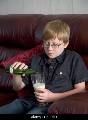 Un garçon de 12 ans est vu verser la lager en bouteille dans un verre - Image