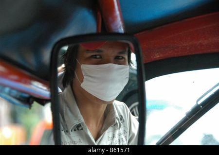 Un conducteur de Tuk-Tuk, portant un masque facial à cause du mauvais air, Bangkok, Thaïlande, Asie - Image