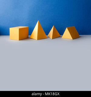 Figures géométriques abstraites. Objets rectangulaires de tétraèdre pyramidal en trois dimensions sur fond gris bleu. Couleur jaune de solides platoniques encore - Image