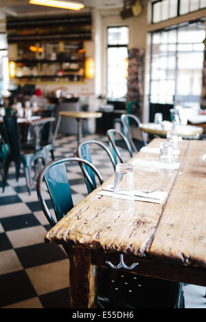 Community table with metal chairs and checkered floor in modern industrial restaurant. - Stock Image