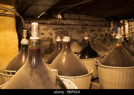 Vin rouge fait maison, stocké dans de grands pichets en verre dans des paniers au sous-sol à l'intérieur d'une vieille maison de style cottage Canadiana vers 1850 - Image