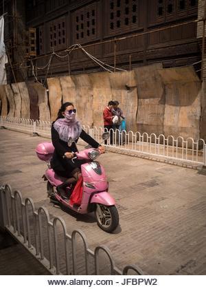 Une femme portant un visage couvrant pour protéger contre la pollution, promenades son scooter moteur passé embarqué bâtiments - Image