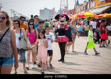 Costumed characters solicit tips on the boardwalk on a seasonably warm Sunday, July 5, 2015 in Coney Island in Brooklyn - Stock Image