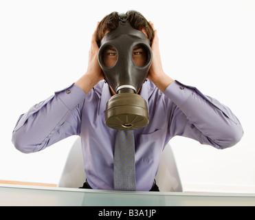 Homme d'affaires assis portant un masque à gaz tenant ses mains sur ses oreilles - Image