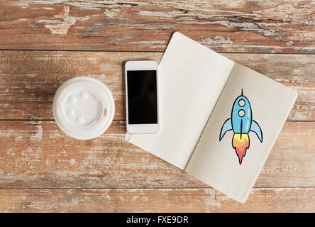 close up of notebook, coffee cup and smartphone - Stock Image
