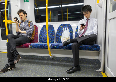 Sydney Australia NSW New South Wales Trains City Circle public transportation onboard cabin riders passengers Asian man looking smartphone messages co - Stock Image
