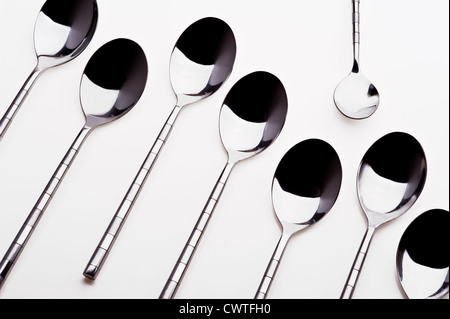 Group of dessert spoons with one teaspoon standing alone. - Stock Image