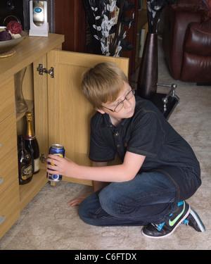 Un garçon de douze ans regarde autour de lui pour voir s'il est surveillé tout en prenant une canette de bière dans une armoire à boissons - Image