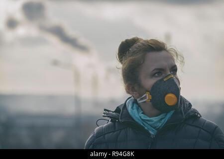 Femme portant un véritable masque anti-pollution, anti-smog et anti-virus; smog dense dans l'air. - Image de l'éditeur
