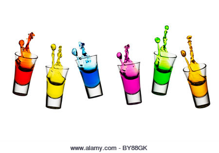 Colorful liqueur spilling from shot glasses - Stock Image
