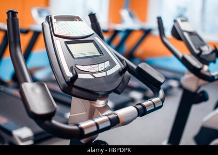 Aerobics spinning exercise bikes gym room with many in a row - Stock Image