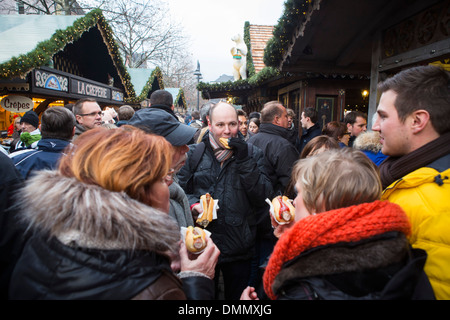 Christmas Market of Cologne: People eating roll sausage at the  Altstadt or older part of the city - Stock Image