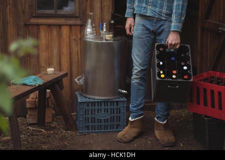 Homme portant des bouteilles de bière en caisse - Image