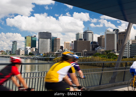 Cyclists on the Goodwill Bridge with the city skyline in the background. South Bank, Brisbane, Queensland, Australia - Stock Image
