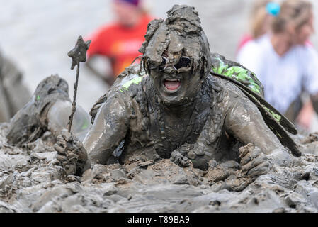 300 runners tackle the course which takes them across the River Blackwater and back at low tide through the clinging mud. The Maldon Mud Race competitors run for charity with many in fancy dress and all get covered in mud during the race. Male angel with wand covered in mud - Stock Image
