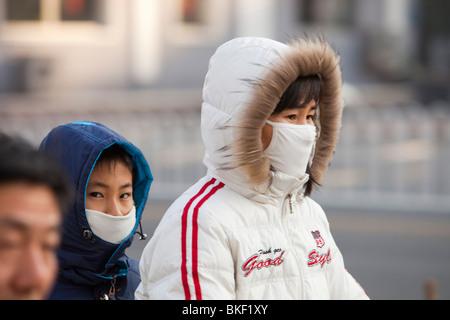 À Beijing, les cyclistes portent des masques de smog pour se protéger contre la pollution atmosphérique. - Image de l'éditeur