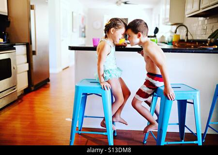 Two children in swim suits being silly at meal time at home in modern kitchen - Stock Image