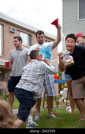 Des garçons s'amusant à boire de la bière avec un tuyau. Grand vieux jour festival st paul minnesota mn usa - Image