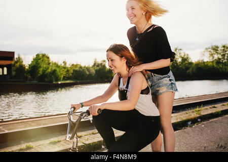 Two friends riding BMX bicycle together - Stock Image