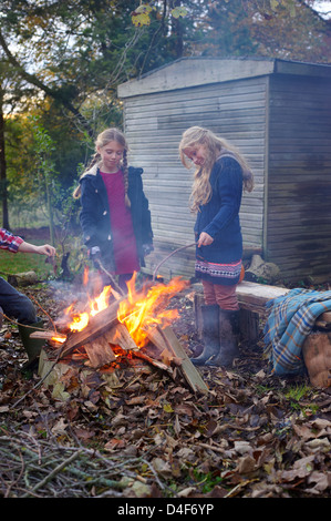 Girls building bonfire outdoors - Stock Image
