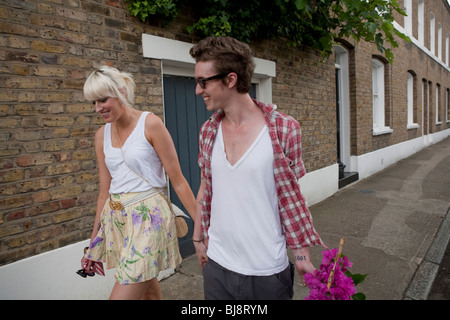Couple walking home from flower market in summer, london, england, uk, europe - Stock Image