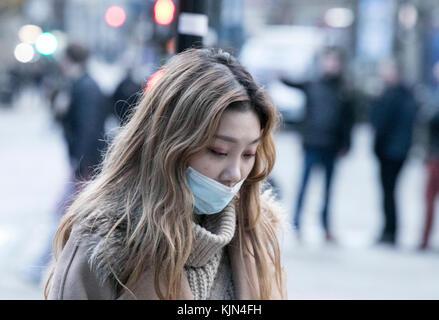 Une fille asiatique ou orientale porte un masque anti-pollution comme elle se promène dans les rues de la ville de manchester, Angleterre, unie - Image