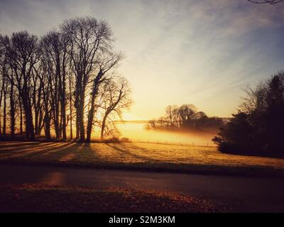 Sun sets over hazy countryside. - Stock Image