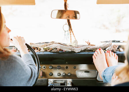 A woman resting her bare feet on the dashboard of a 4x4, on a road trip with another woman driving. - Stock Image